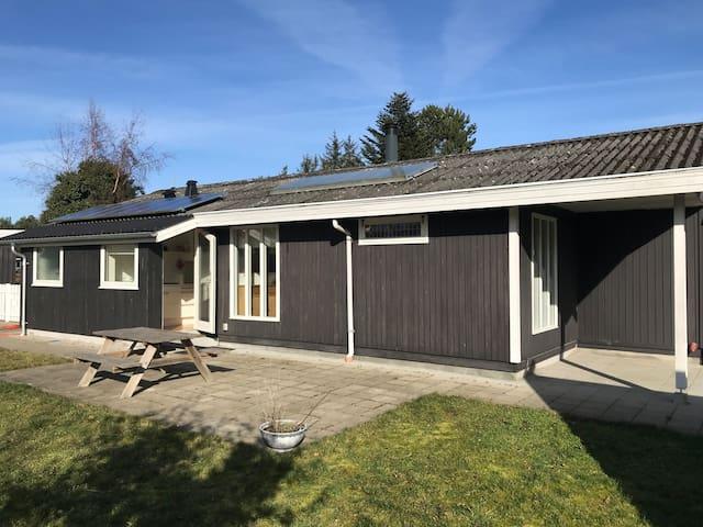 Hus med solfanger og solceller tæt ved havet