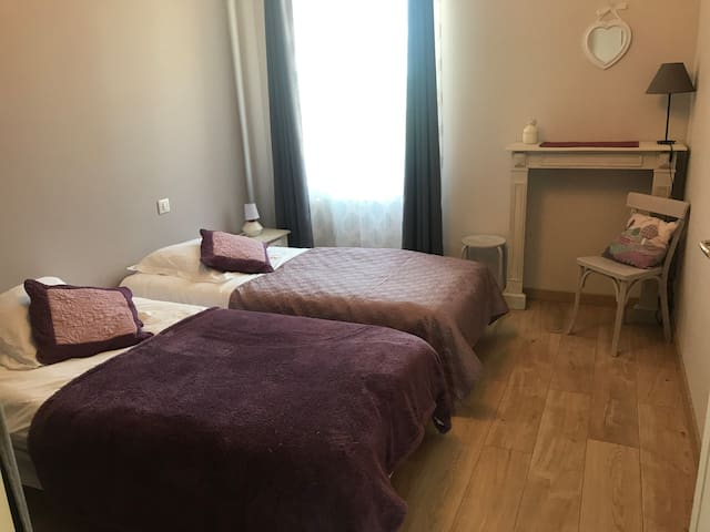 Deux lits de 90x190, deux chevets et dressing dans la chambre lilas