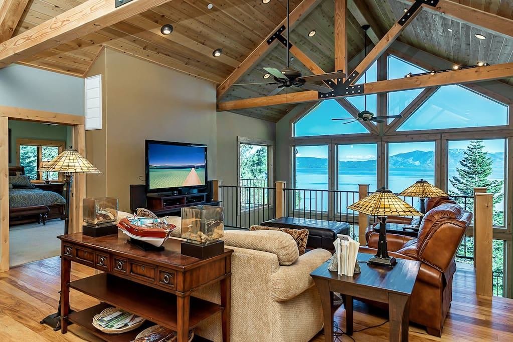 Abundant natural light fills the first living area with a plasma screen TV.