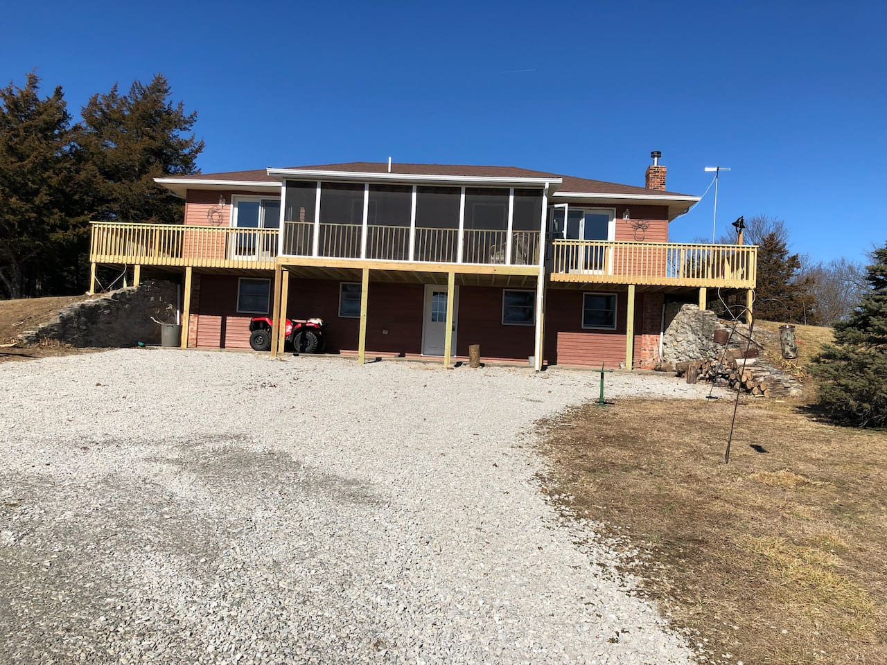 Front of house with screened-in patio and two wrap around decks. One deck is off living room and other is off master bedroom. Can access screened-in room from either side. Food plot visible from this location which is frequented by deer and turkey.