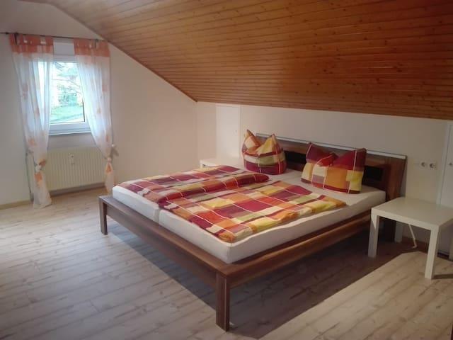 Das Schlafzimmer mit Doppelbett und Babybett