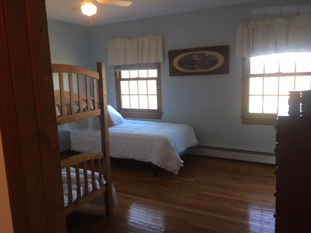 Bedroom 4 - Features bunk beds and twin bed, dresser, closet, chair and view of the front of the property