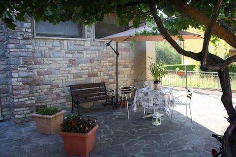 Zona esterna con panchina, tavolo, sedie e un ombrellone per ripararsi dal sole
