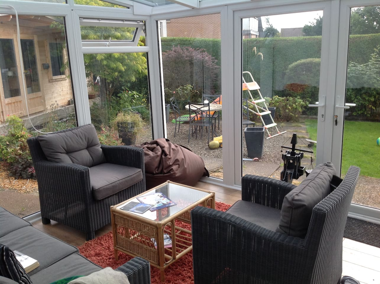 Conservatory opening into shared garden.