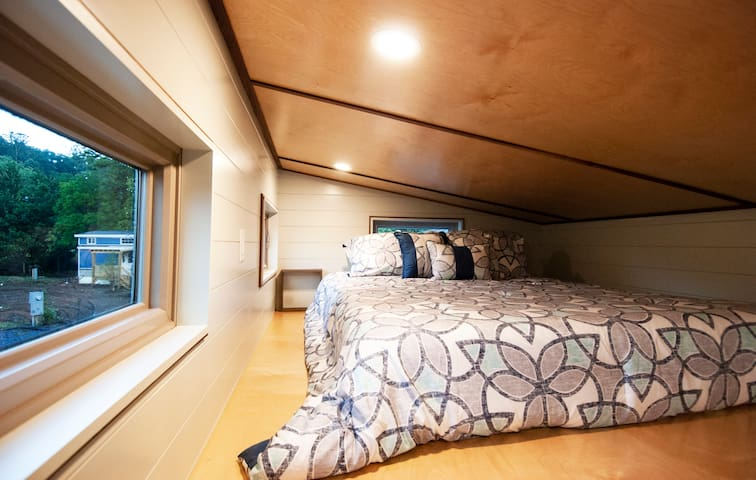 Main loft features queen sized bed with mountain views outside the window.
