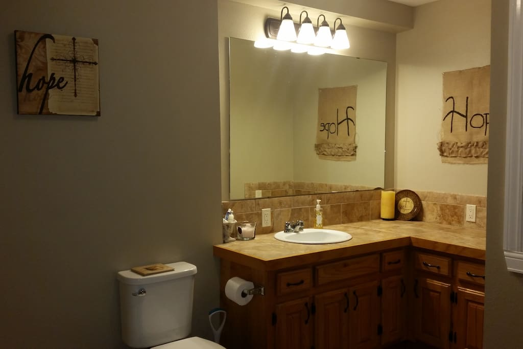 Spacious bathroom with shower and tub. Equipped with hair dryer, Basic toiletries, and fluffy towels.