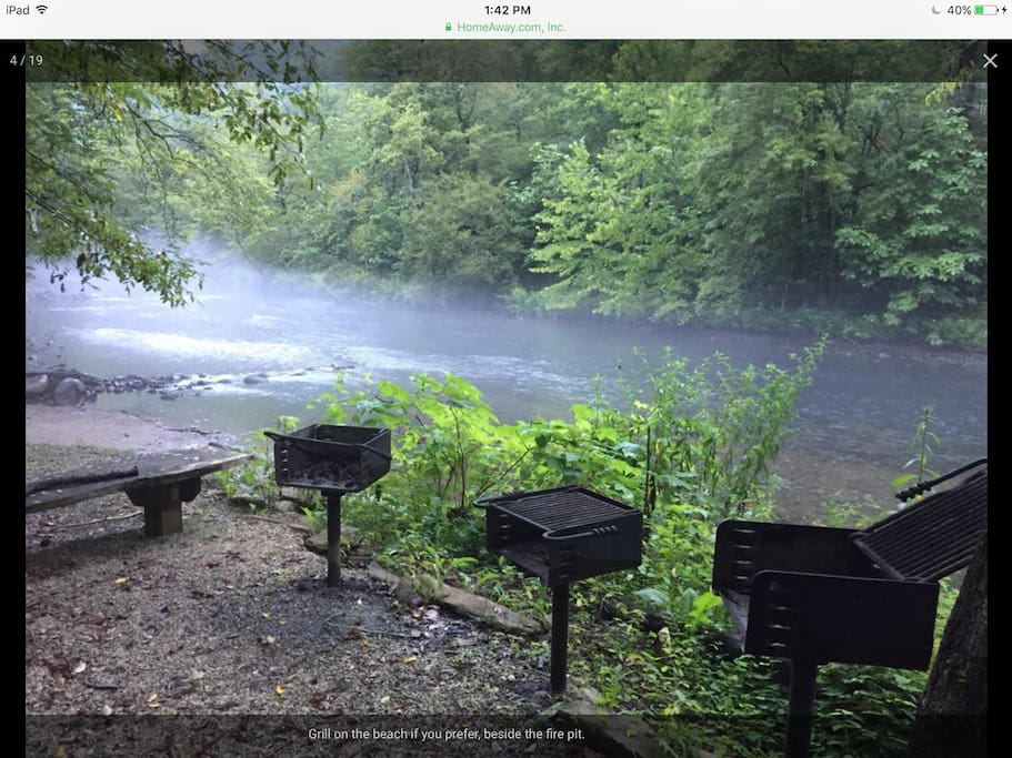 Seating and grilling beside river house.