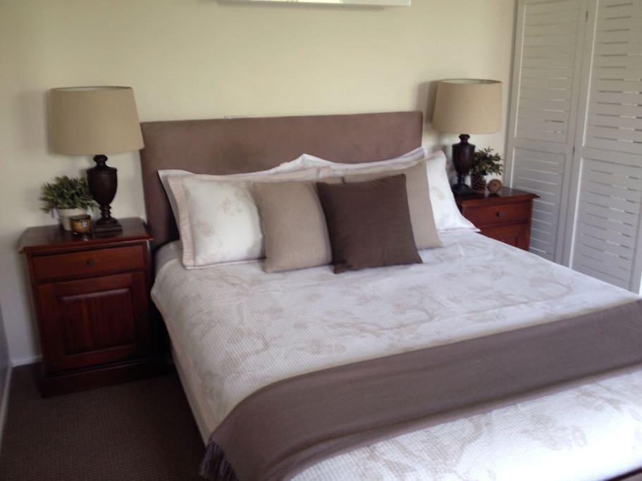 Bedroom with queen size bed, luxury linens, bedside tables and lamps. Features pure wool carpeting throughout and a private view over the garden.