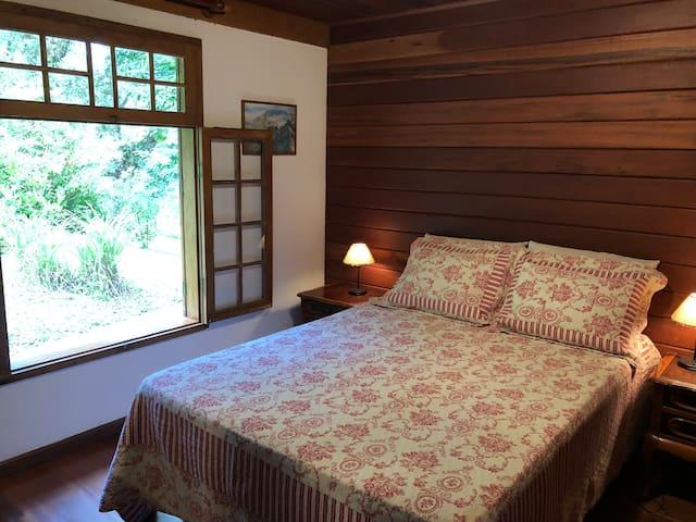 Quarto do Chale com grande janela de madeira com vista para natureza