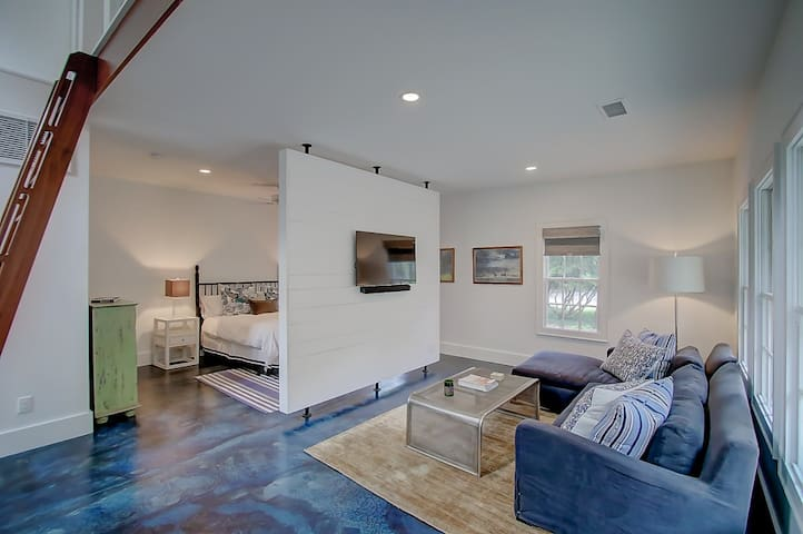 Open living area with wall separating the bedroom.