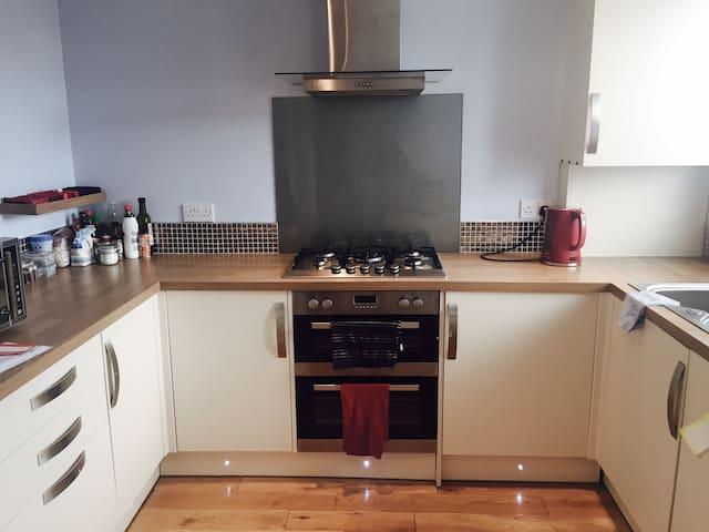 Modern shared kitchen with kitchenware, cockers, ovens, microwave, fridge and freezer, dish washer and washing machine.