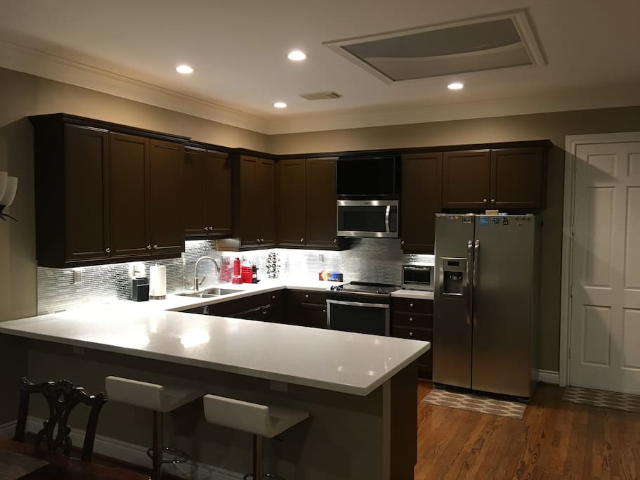 Open concept kitchen with stainless appliances, silestone countertops, hardwood floors, and custom lighting