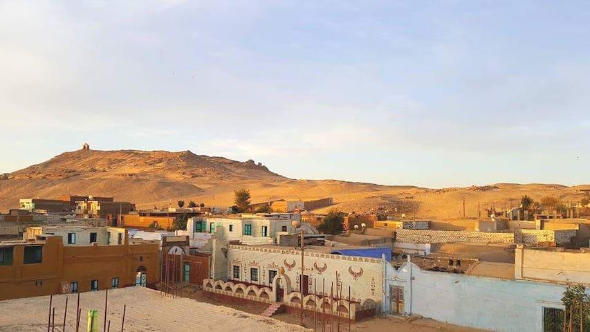 Blick vom Wohnzimmer auf die Felsengräber und das Dorf