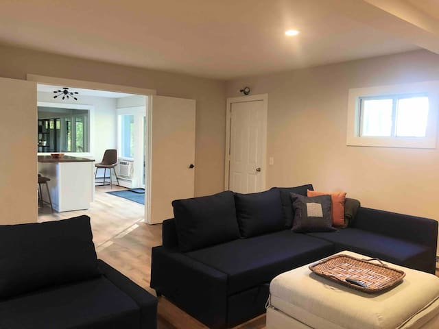 """Family Room off kitchen with two sleeper sofas and two ottomans that convert into twin beds. New 65"""" Samsung Smart TV."""