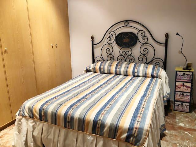 Habitación con cama de matrimonio en el salón con chimenea