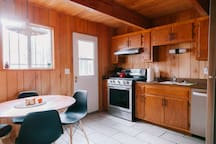 Kitchen with new appliances (fridge, stove/oven, and dishwasher) and a dining table that comfortably seats 4 to 5 people.