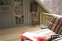 Deck facing north under the canopy of a big white pine with 2 lounge chairs and table for 2