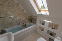 ENSUITE BATH w. WHIRLPOOL TUB,  TV & overhead shower in ensuite one.  Robes, slippers, toiletries provided.