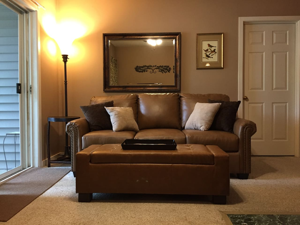 Warm, inviting living room with leather sleeper sofa (queen memory foam mattress). Door to master bedroom seen to right of couch.