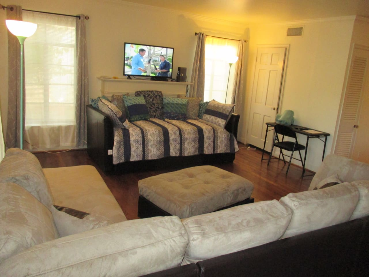 Living room with sofa sectional and daybed which has 2 twin size mattresses, accommodating 2 people.