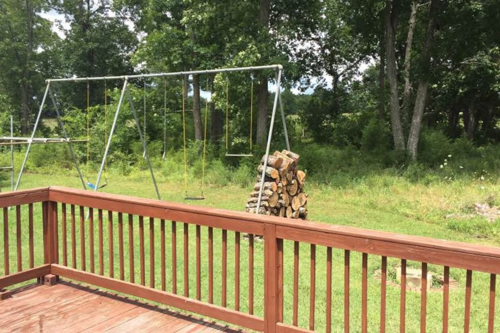 Backyard with large swingset, in-ground fire pit with wood.