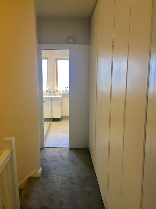 Hallway leading to upstairs bathroom has wardrobes all along it.