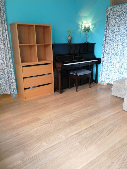 Country Living Room: William Morris vintage curtains made in Walthamstow, vintage piano, stackable storage units, entertainment system.