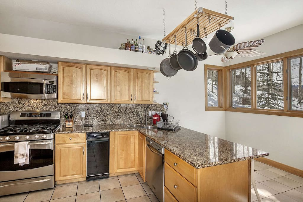 The fully equipped kitchen boasts granite counter tops and stainless appliances.