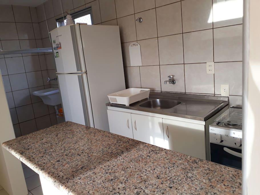 Visão da cozinha,  tanque de lavar roupa e varal