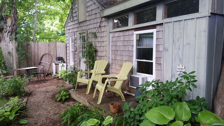 As you approach the front door of the Tiny House you can see the tiny porch with two plastic Adirondack chairs. There is an AC in the bedroom window now, to improve cool temps and airflow.