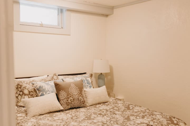 Close up of queen size bed in private bedroom.  Sound machine is bedside for those who prefer white noise to nature!