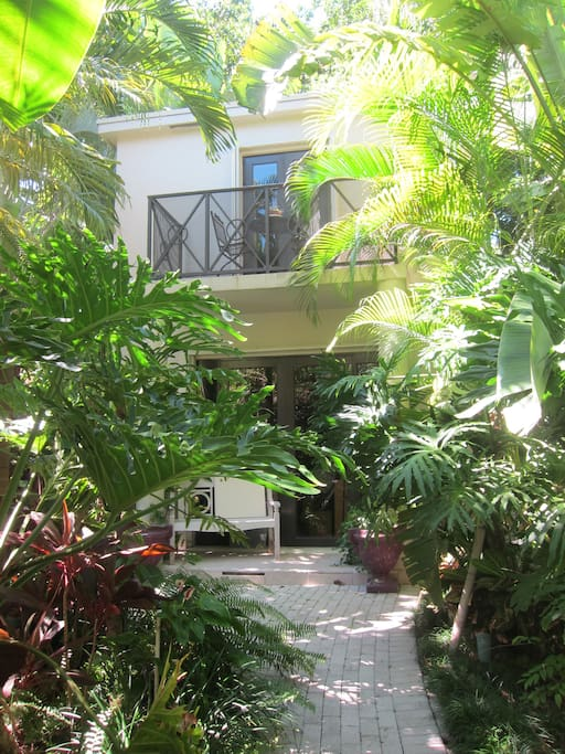 2nd floor guest suite in guesthouse set in lush tropical setting of main house.