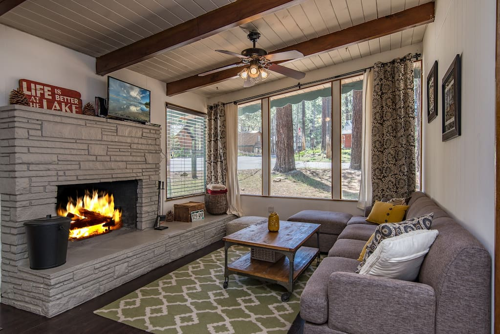 Cozy up by the fire in this welcoming living area with stone fireplace and seating for four.