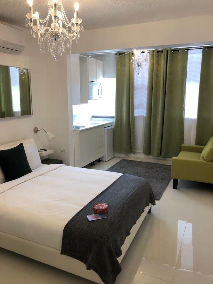 Vista del cuarto de habitación el cual incluye toallas y ropa de cama,mesa de noche con lámpara, closet, butaca, TV con sistema ROKU, Internet y una cama Queen para 2 personas.