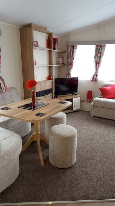 Living area with LED TV, DVD and CD player, a selection of DVD's and a pack of cards for rainy days!