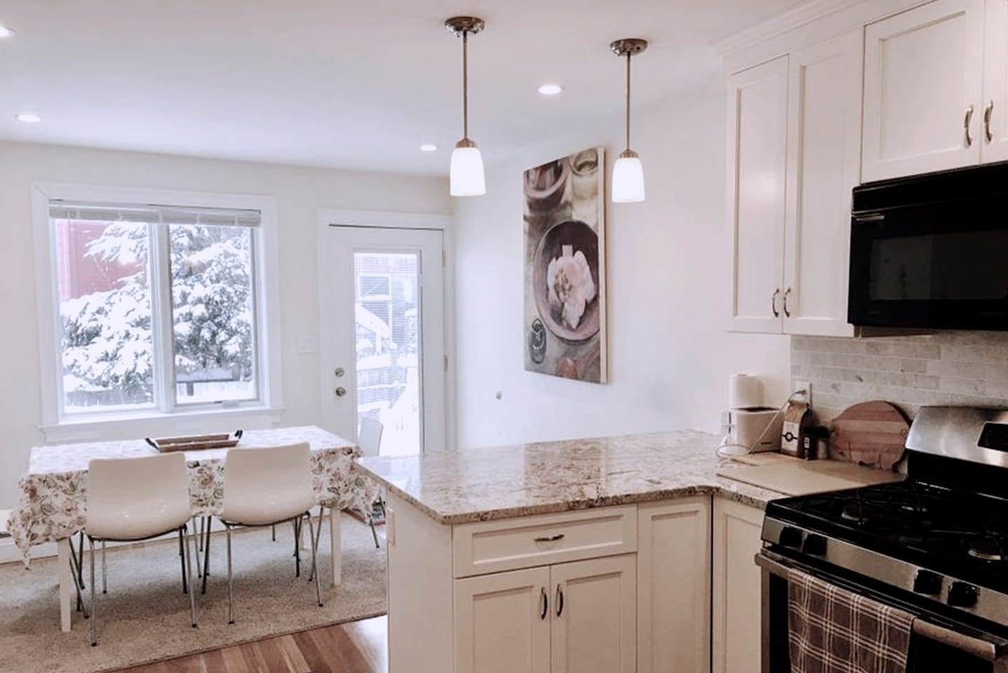 Granite kitchen with stainless steel appliances and open dining room