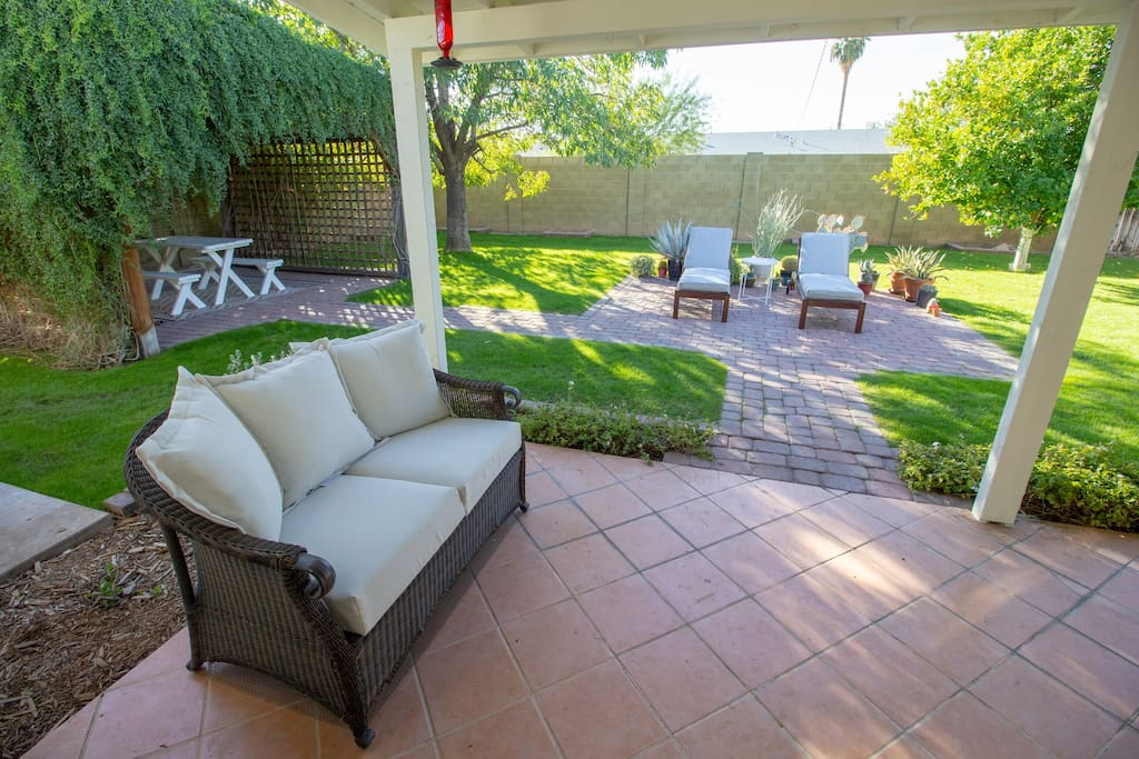 Back Patio | Two chaise lounges, a picnic table under the pergola, and a comfy outdoor sofa.