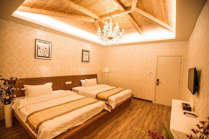 家庭房,两张一米五的榻榻米式大床,可以睡4个人,适合一家三口或者一家四口出行。房间宽敞,风格偏欧式,天花板带一个大水晶吊灯