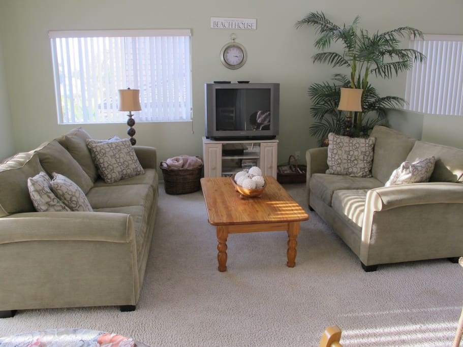 Queen sleeper sofa and love sofa bookend living room  with cable TV/wireless internet.