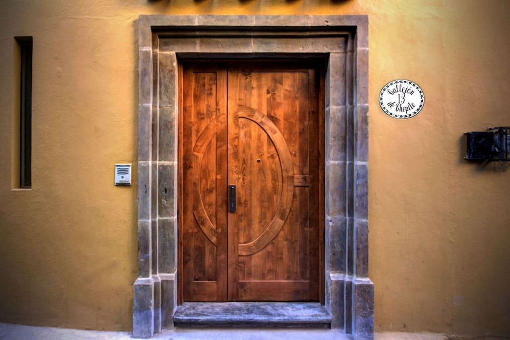 Your vacation awaits through the cantera stone and wood doors, from the callejon.