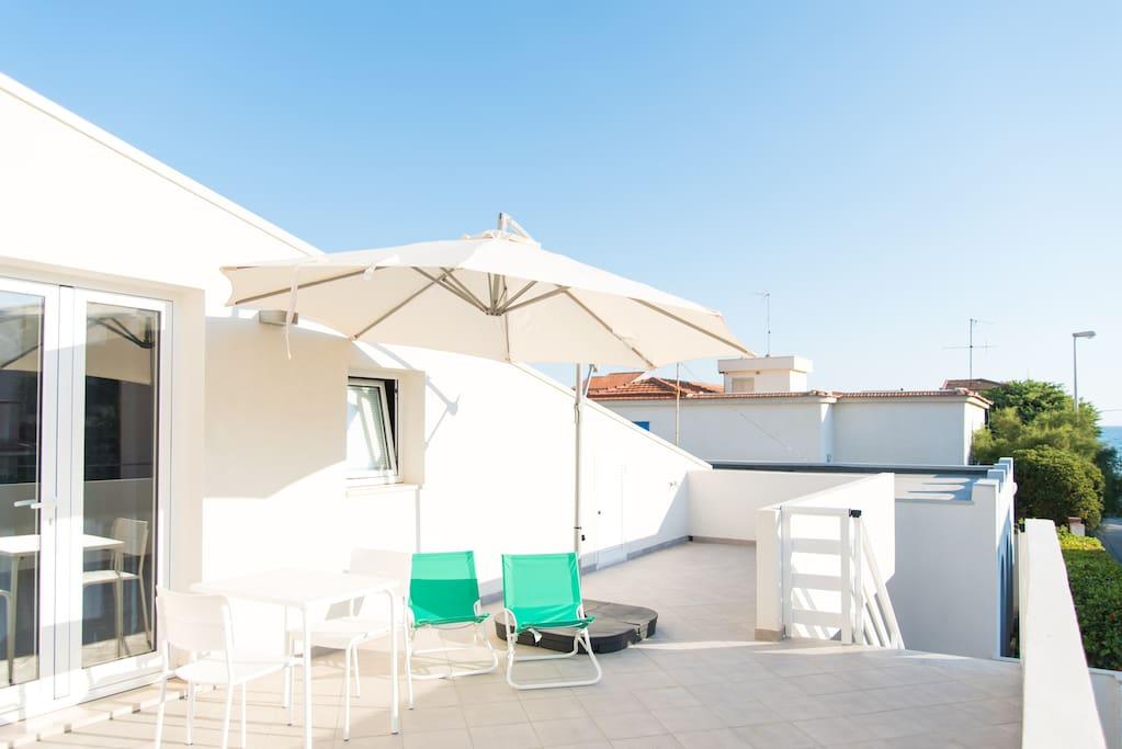 Ampia veranda esterna con area solarium e veduta mare