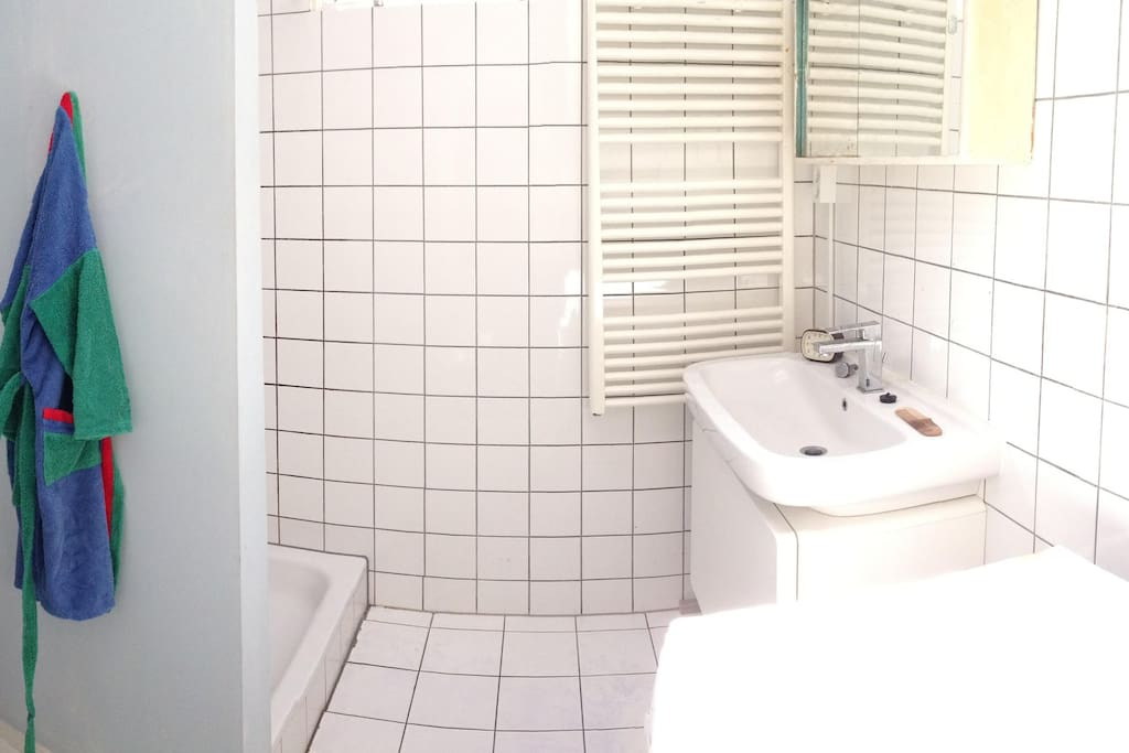 Clean bathroom with big shower, toilet and washing machine.