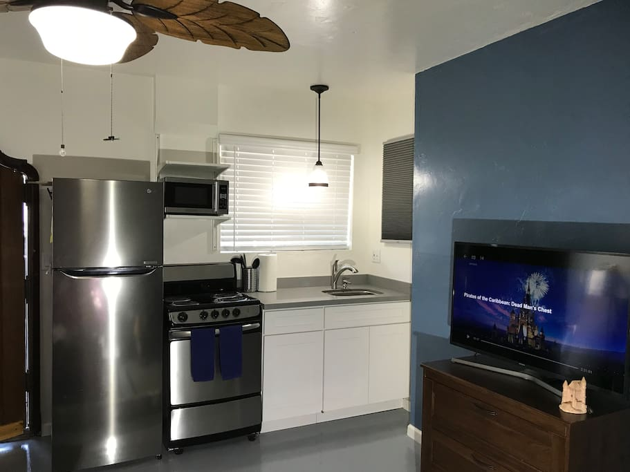 new kitchen with refrigerator, oven, stove, microwave, sink and quartz countertop