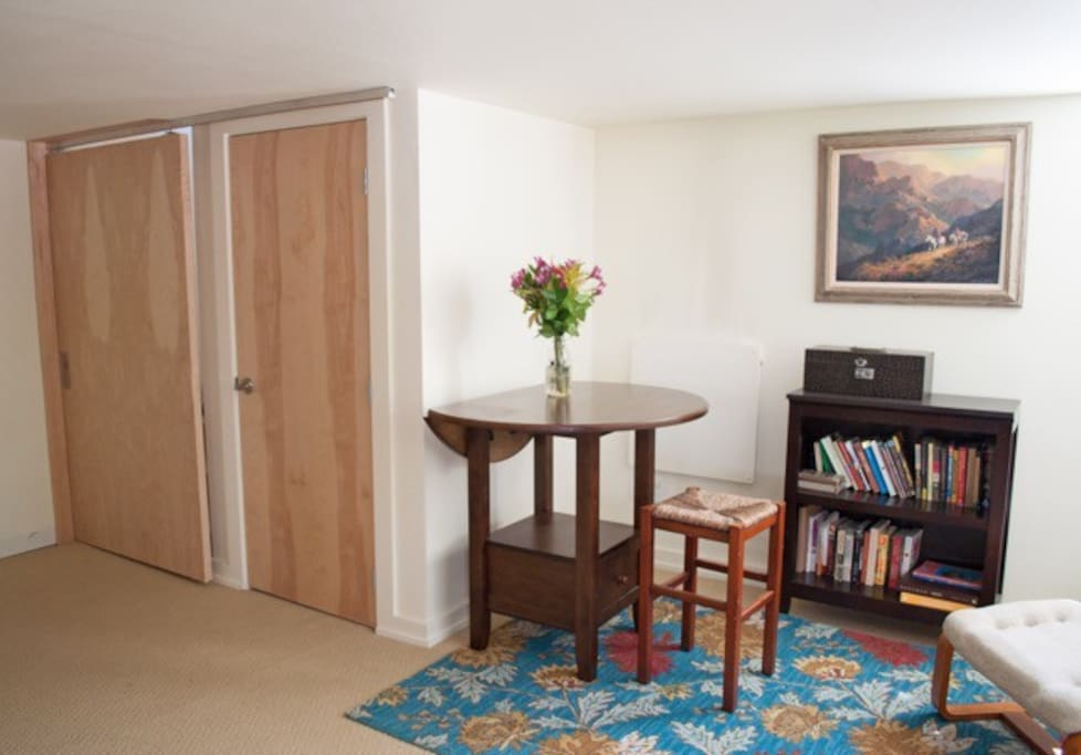 """Small """"dining"""" area and reading nook. Door on the right is a closet with linens, towels and other essentials. On the left is a locking """"barn"""" door that separates upstairs and downstairs."""