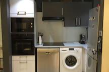 Cuisine ouverte - plaque à induction - lave-vaisselle - lave-linge - réfrigérateur-congélateur - four électrique - four micro-ondes - machine à café Nespresso.
