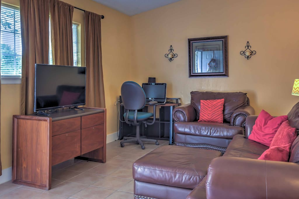 Walk into this charming home and take a seat in the living room featuring a sumptuous leather couch, leather armchair, computer, and flat-screen satellite TV.