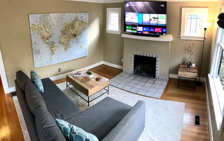 """Living room with 65"""" smart TV, access to Netflix and Hulu. The couch pulls out to become a queen sized sleeper and is very comfortable!"""