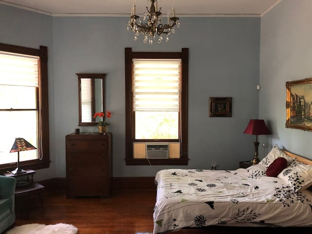 Downstairs queen with original mahogany trim, chandelier, lovely bay windows and lots of space.