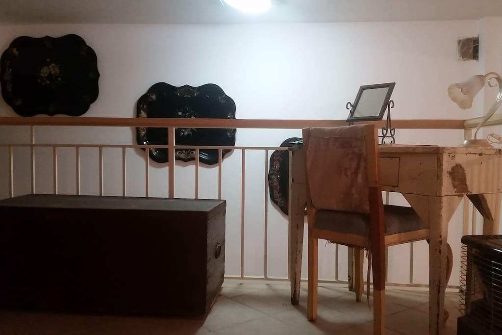 Lo spazio comune, sopra il soppalco del soggiorno. Un angolo lettura e studio, ricco di libri e dal design vintage.