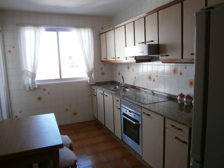 Cocina con vitro, horno, frigorífico y lavadora